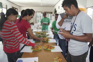Farmers and MAF-SoL researchers tasting the different sweet potato varieties